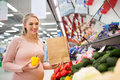 Pregnant woman buying vegetables at grocery store Royalty Free Stock Photo
