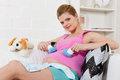 Pregnant  woman with children's clothes. Stock Photos