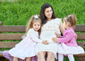 Pregnant woman and children in summer city park outdoor, happy family, bright sunny day and green grass, beautiful people portrait Royalty Free Stock Photo