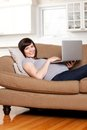 Pregnant woman with computer happy using in living room Stock Photos