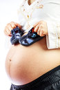 Pregnant woman with cute shoes for the baby on her belly. Royalty Free Stock Photo