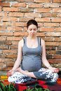 Pregnant woman doing yoga young caucasian sitting in relaxation pose by brick wall outdoor Stock Photos