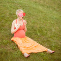 Pregnant woman enjoying summer park holding a paper red heart outdoors new life concept Royalty Free Stock Photography