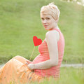 Pregnant woman enjoying summer park holding a paper red heart outdoors new life concept Stock Image