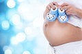 Pregnant woman expecting boy holding blue baby booties Royalty Free Stock Photos