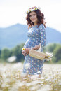 Pregnant woman in field with basket of white daisies Royalty Free Stock Photo