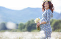 Pregnant woman in field with bunch of daisies Royalty Free Stock Photo