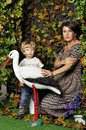 Pregnant woman with her child in garden looking studio style touch stork women Stock Photography