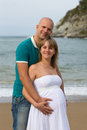Pregnant woman and her husband embracing by the sea happy women Stock Photography
