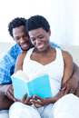 Pregnant woman and her husband reading book women at home Royalty Free Stock Photos