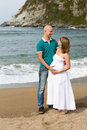 Pregnant woman and her husband strolling by the sea happy women Stock Image