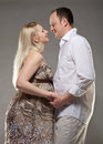 Pregnant woman with her husband women grey background Stock Image