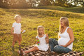 Pregnant woman with her kids beautiful blond women enjoying older company mother outdoors in sunlight mother s day concept Stock Photography