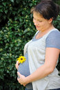 Pregnant woman holding her belly and yellow flower Stock Images