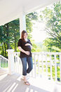 Pregnant woman at home a portrait of a on a porch holding her belly Royalty Free Stock Photography