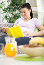 Pregnant woman in home resting and reading book lying on a sofa a Stock Photography