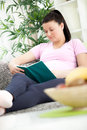 Pregnant woman in home resting and reading book lying on a sofa a Stock Photos