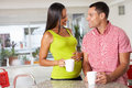 Pregnant woman and husband having breakfast in kitchen smiling to each other Stock Photo