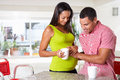 Pregnant woman and husband having breakfast in kitchen smiling to each other Royalty Free Stock Images