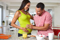 Pregnant woman and husband having breakfast in kitchen smiling to each other Royalty Free Stock Photography