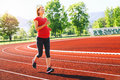 Pregnant woman jogging on running track in stadium. Royalty Free Stock Photo