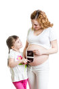 Pregnant woman and kid daughter reviewing baby ultrasound sc women her scan Royalty Free Stock Photos