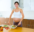 Pregnant woman at kitchen preparing salad Royalty Free Stock Photography