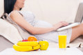 Pregnant woman with laptop beautiful working on while lying on a couch Royalty Free Stock Image
