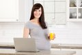 Pregnant woman with laptop computer happy in kitchen using Royalty Free Stock Photo