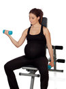 Pregnant woman lifting weights in the gym isolated on a white background Stock Photo