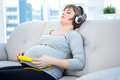 Pregnant woman listening to music with eyes closed at home Stock Image