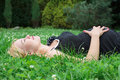 Pregnant woman lying on the grass with eyes closed Royalty Free Stock Photo