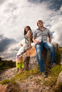 Pregnant woman and man sitting women men on rock Stock Photography