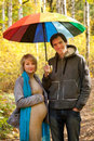 Pregnant woman and a man walking under umbrella beautiful women men in the autumn forest rainbow colorful Royalty Free Stock Photo