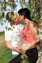 Pregnant woman and man women men in the park kiss Royalty Free Stock Image