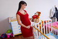 Pregnant woman near baby cradle Stock Photo