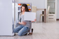 The pregnant woman near fridge with blank message
