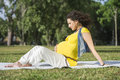 Pregnant woman in outdoor portrait of relax green park Stock Photos