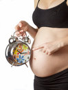 Pregnant woman pointing at alarm clock Stock Photo