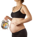 Pregnant woman pointing at alarm clock Royalty Free Stock Image