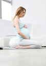Pregnant woman practicing yoga in the living room Stock Image
