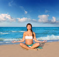 Pregnant woman precticing yoga in blue beach Stock Images