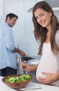 Pregnant woman preparing a salad in the kitchen women with her husband washing dishes behind Stock Image
