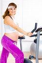 Pregnant woman preparing for workout on bicycle Stock Photos
