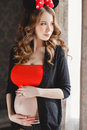 Pregnant woman with red bow. Royalty Free Stock Photo