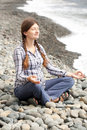 Pregnant woman relax doing yoga on beach meditating a rocky near the sea line Royalty Free Stock Photography