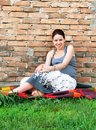 Pregnant woman relaxed happy smiling young caucasian sitting by brick wall outdoor Stock Photo