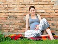 Pregnant woman relaxed happy smiling young caucasian sitting by brick wall outdoor Royalty Free Stock Photos