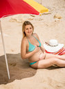 Pregnant woman relaxing in the shade of parasol on beach beautiful Royalty Free Stock Images