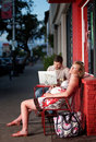 Pregnant woman resting outside on a chair Royalty Free Stock Photo